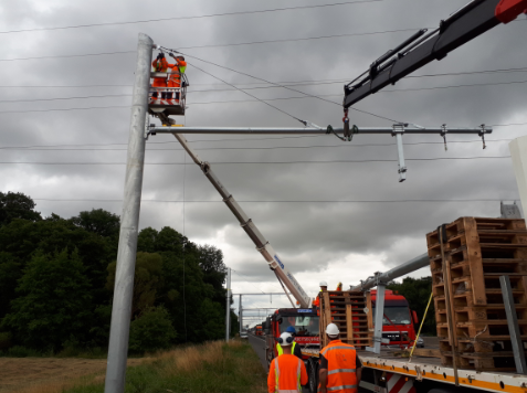 Construction workers work on overhead lines on a lift