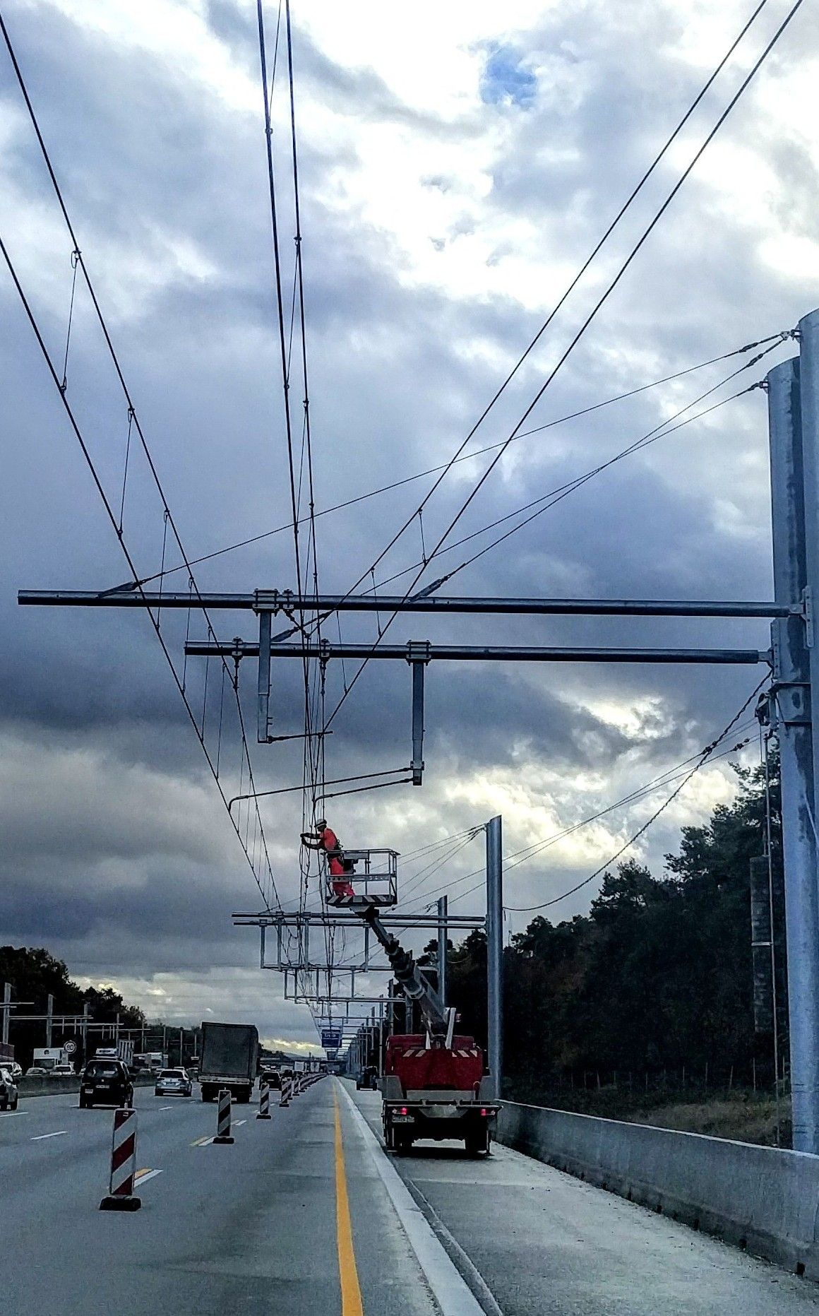 Construction worker works on overhead lines on a lift